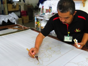 Drawing the pattern freehand on a swathe of silk. Batek display, Malaysia
