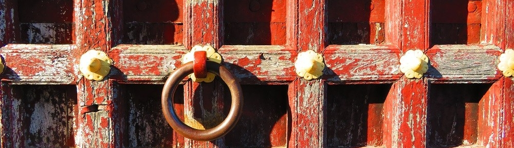 A rustic timber door with pealing paint and a heavy brass ring