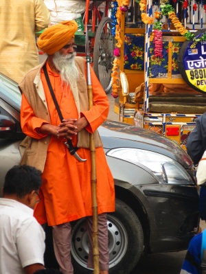 Man in an orange turban leans on a car in the street in Delhi