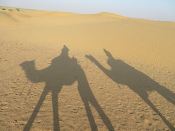 Shadows of camels and riders on sand dunes