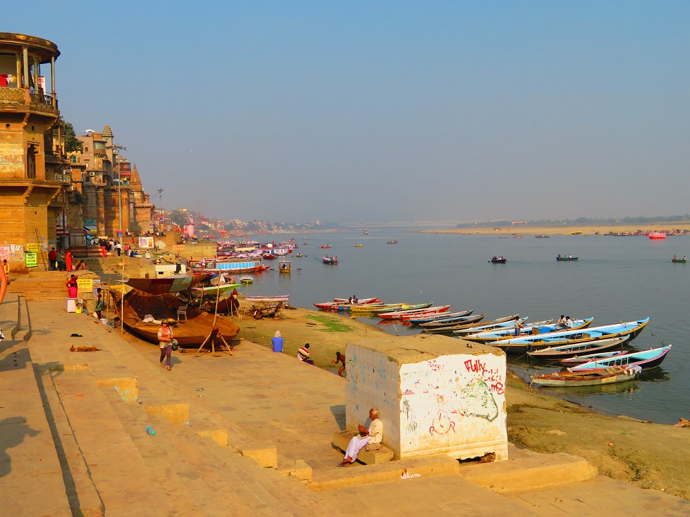 A view along the ghats next to the river Ganges. Many boats in the river await passengers