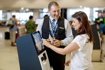 A woman checks in for her flight with the assistance of an information man