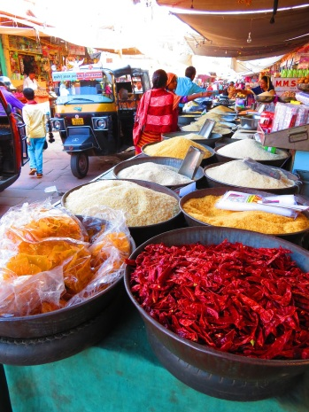 Large dishes containing a brightly coloured spices in a market