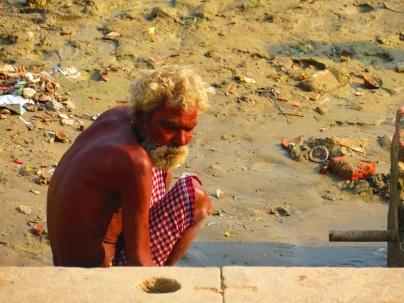 An old man waits at the river's edge, Varanasi, India