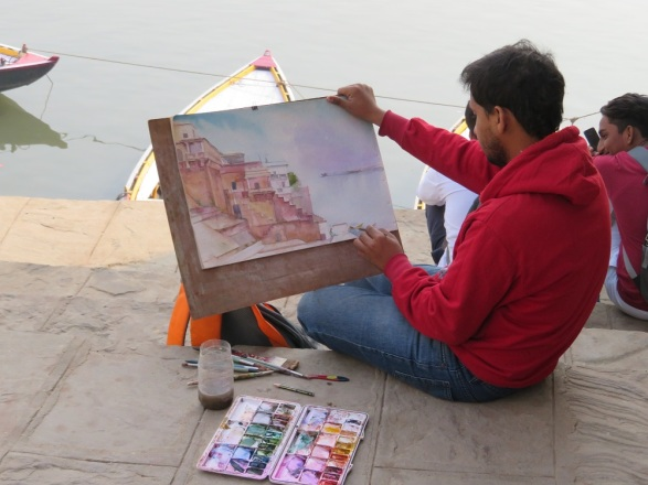 A man paints a water colour of the Ghats at Varanasi
