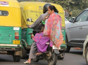 Lady on the back of a motor bike in Delhi