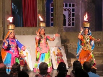 three ladies dancing with fire on their heads