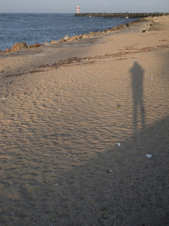 Silhouette on the sand with light house
