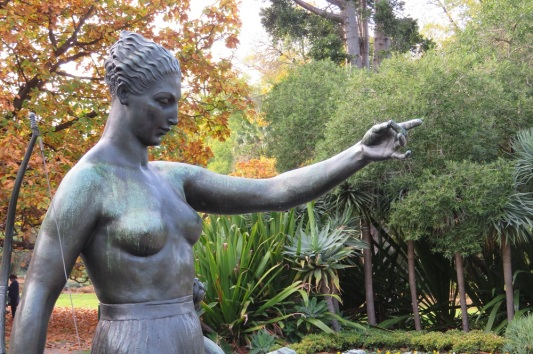 A sculpture of a woman points the way