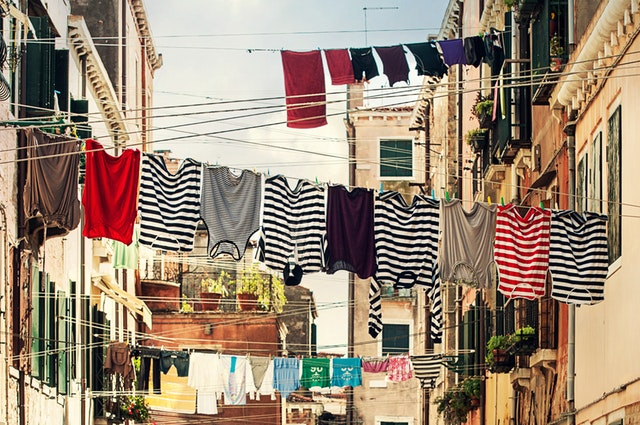A clothesline extending across a street with brightly coloured shirts