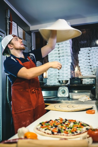 Man throwing a pizza