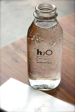 A glass bottle of water - H2O