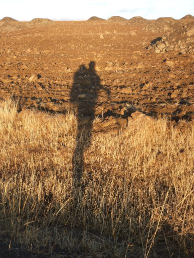 A backpacker's shadow on a paddock