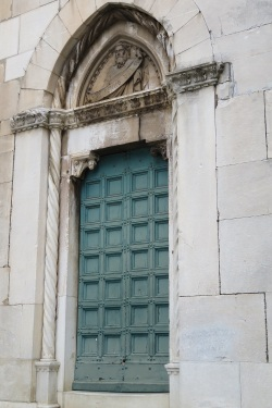 A large green wooden door in Italy