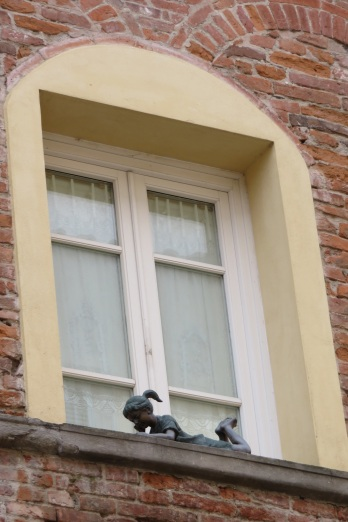 A sculpture of a little girl reading book on a window sill in Lucca Italy