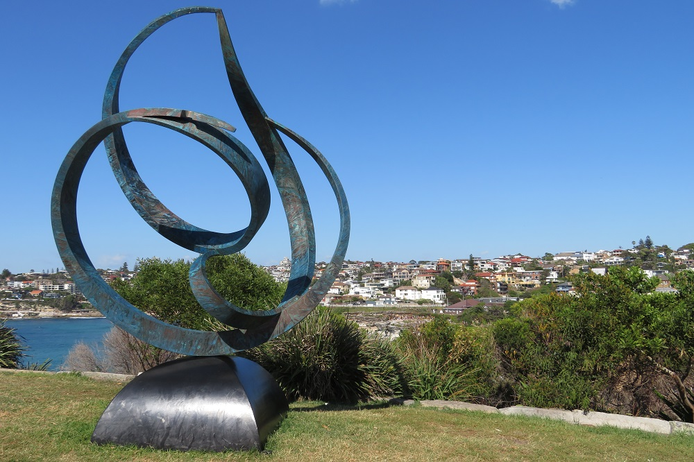 A swirly sculpture with water in the background, Sculpture by the Sea