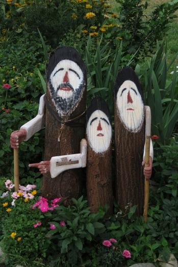 three wooden pilgrim sculptures