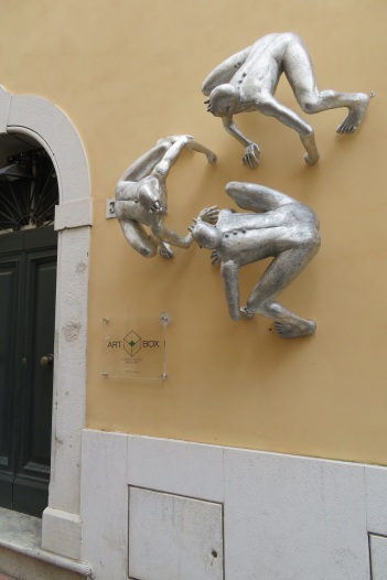 Three silver figures crouch on a wall in Pietrasanta