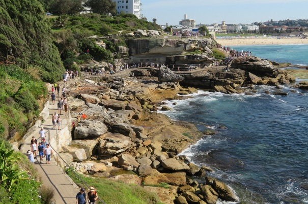 People walking on the cliff path and enjoying Sculptures by the Sea. Bondi Beach in the background