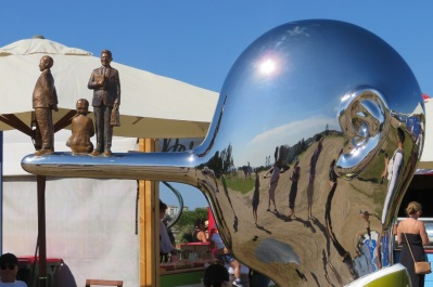 A shiny man's head with a long pointy nose and three people are standing on the nose