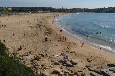 People walk and swim along Bondi Beach