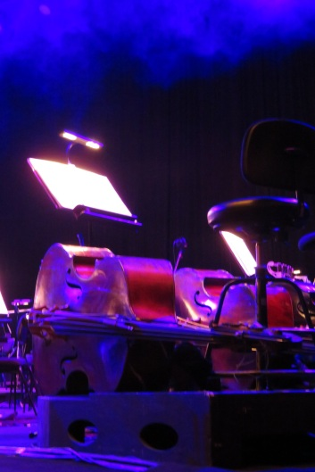 Two double bass lying on their sides on a stage
