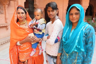 Two Indian women in brightly coloured saris, a young Indian man and a baby