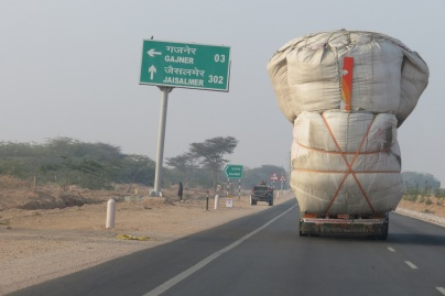 A large truck is overloaded with stock feed