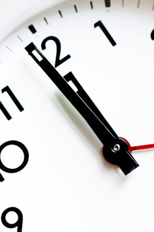 A white clock with black numbers and hands strikes 12