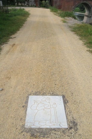 A marble stone, engraved with the Via Francigena logo, is inserted into a dirt path to indicate direction