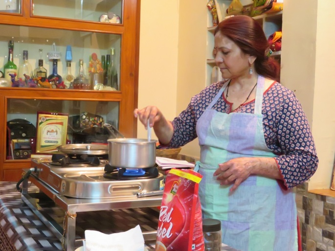 Mrs Shivani cooking masala chai at a stove