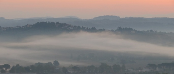 Sunrise in Tuscany, Italy. Mist hangs over the grey valley as the sky turns pink