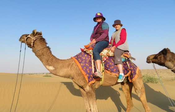 Two people ride a camel in the Thar Desert