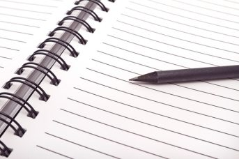 A lead pencil rests on a lined page in a new Notebook