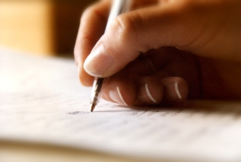 A woman's hand writing on a page with a ball point pen