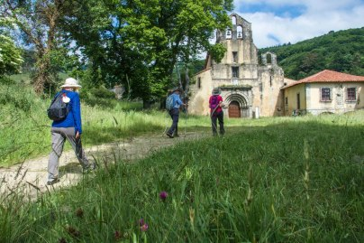 People walk past old buildings on the Camino Primitivo in Spain
