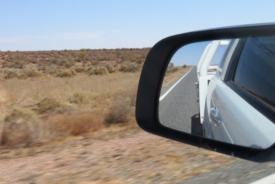 Dry landscape is reflected in the side mirror of a car - Western NSW