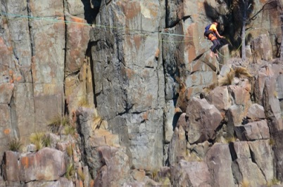 A tightrope walker balances on a line along the Tasmanian coastline