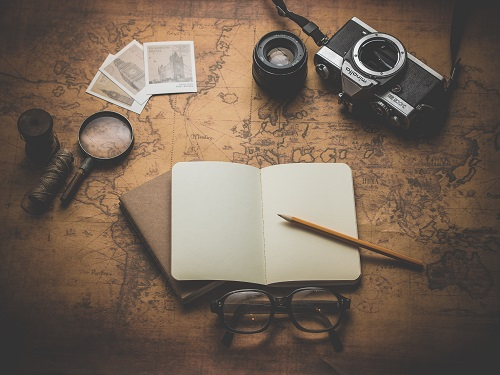 An open travel journal, camera and map of the world
