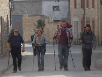 The cast of The Way walk the cobbled streets of a village in Spain