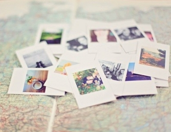 A selection of polaroid photos laying on top of a map
