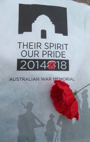 An image of the Australian War Memorial with a red poppy laying across the image