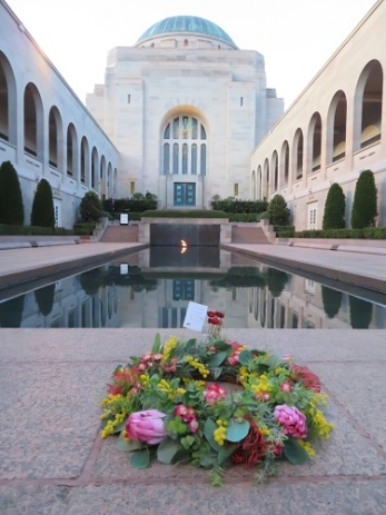 A wreath is placed in front of the Pool of Reflection at the Australian War Memorial