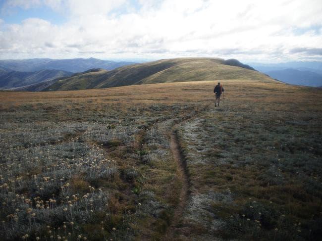 A hiker walks across a high mountain in the Australian Alps