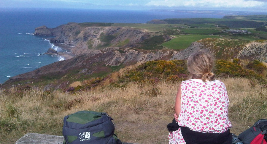 A woman sitting on a cliff enjoying the views of the Cornwall Coast