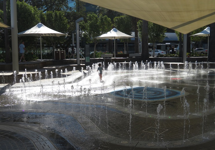 A child runs and frolics in the water park at Elizabeth Quay